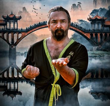 Máday Norbert Wing Tsun Kung Fu nagymester formagyakorlat bemutatása közben egy szép kínai tradícionális hidas folyós hegyes háttérrel